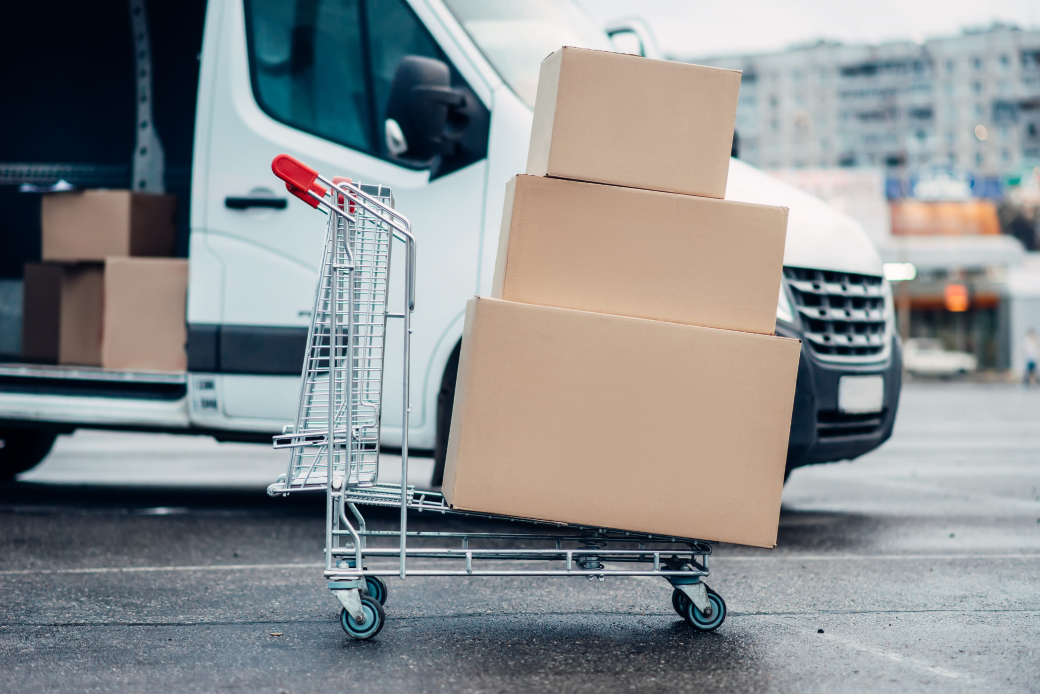 Trolley with carton boxes against truck . Distribution business. Cargo delivery. Empty, clear containers. Mail logistic and post service