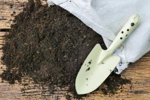small soil shovel next to a bag of soil